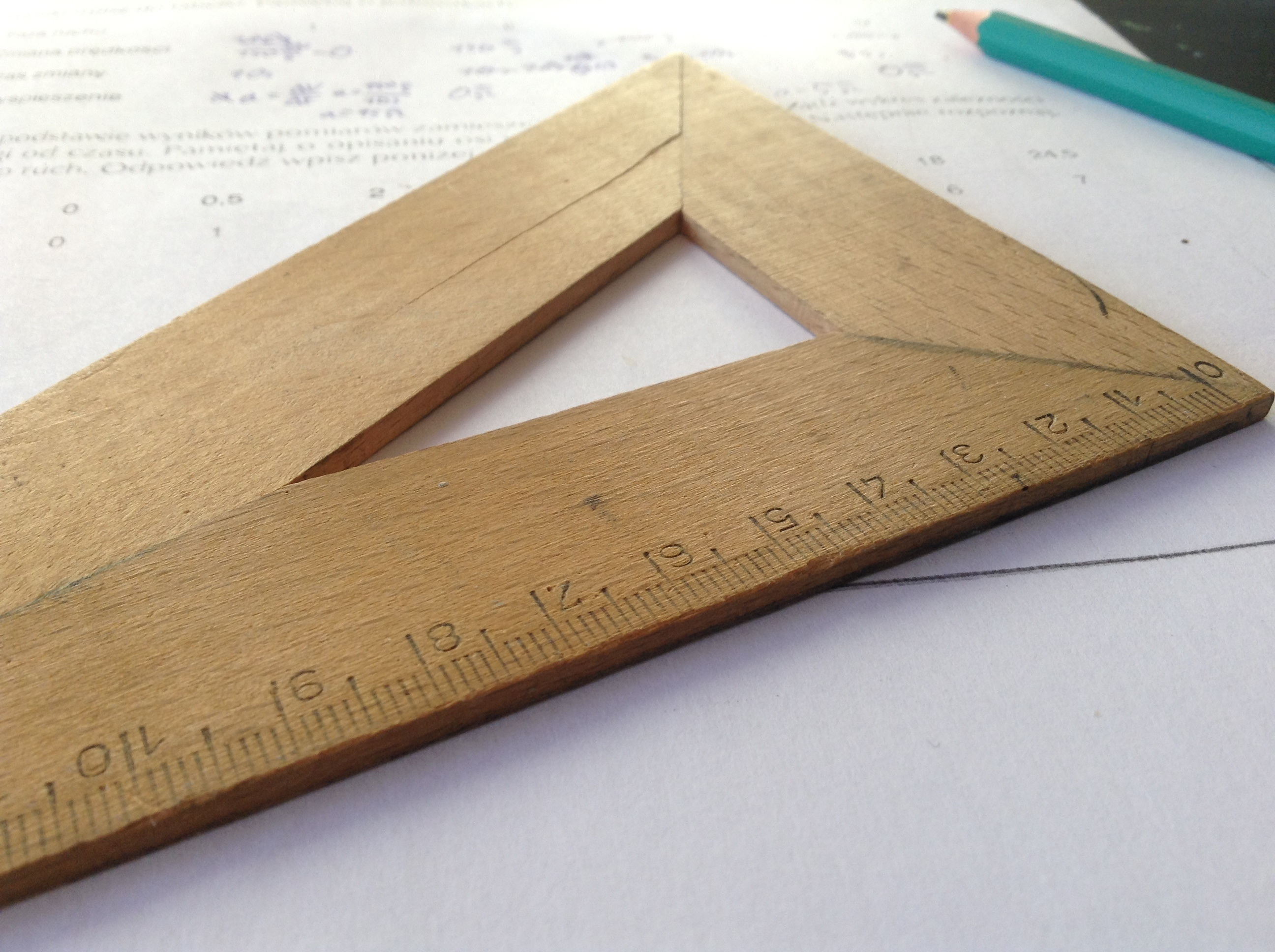 Wooden ruler with math sheet in the background