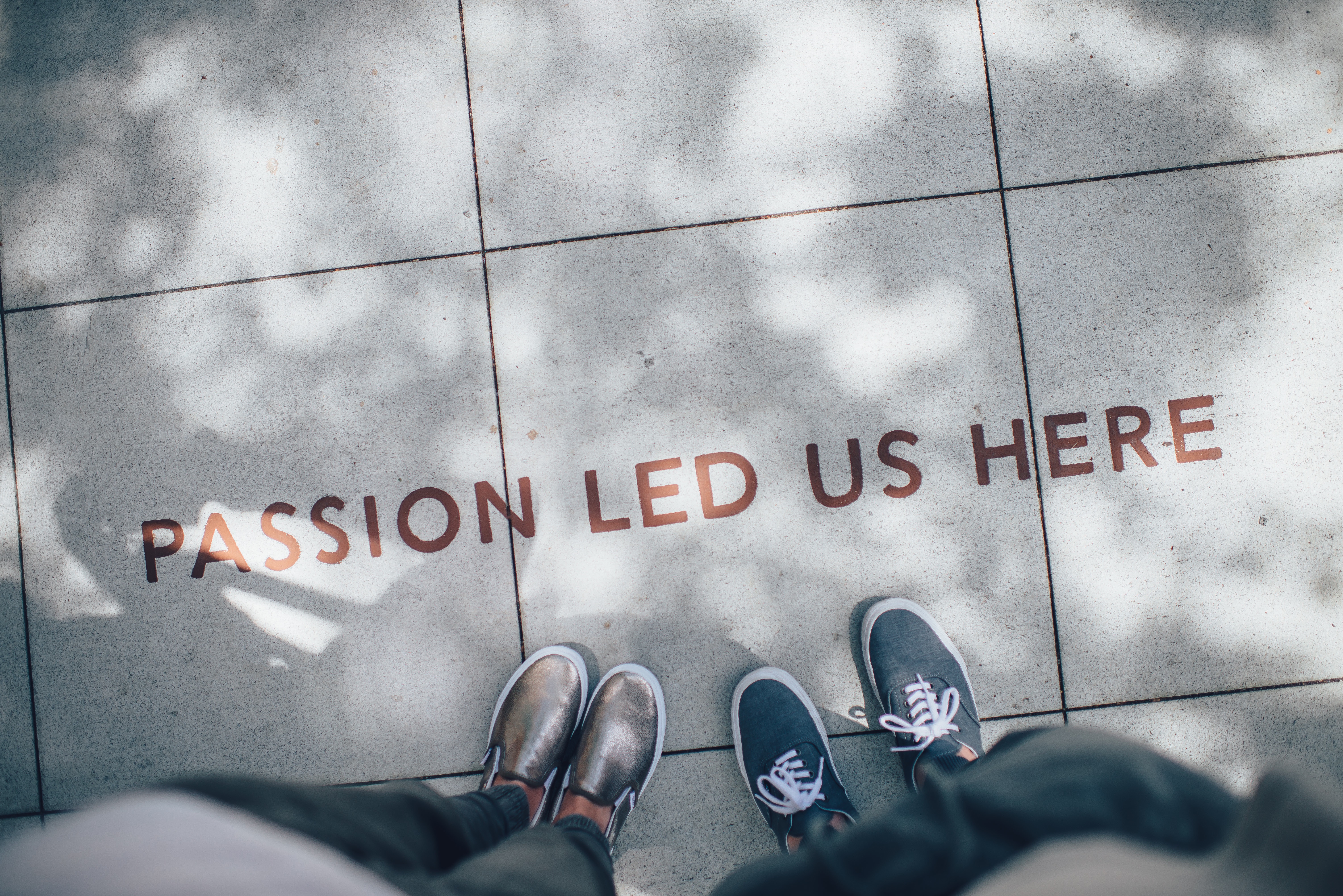 """Sidewalk says """"Passion led us here"""" with two peoples feet"""