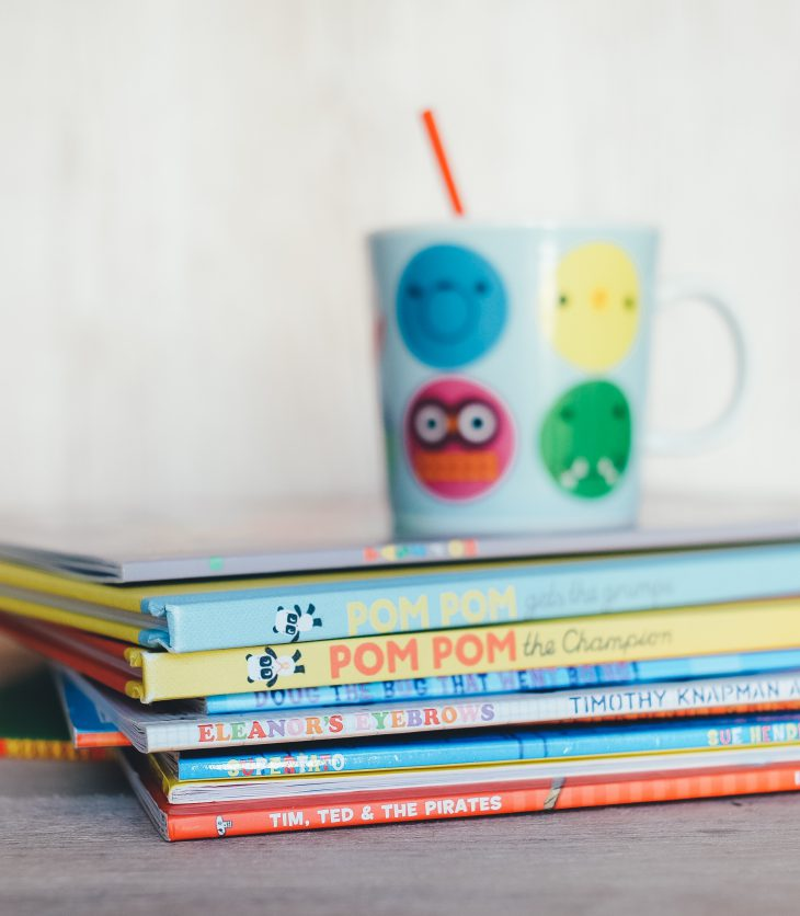 Photo of a colorful coffee mug on top of a stack of books for youth