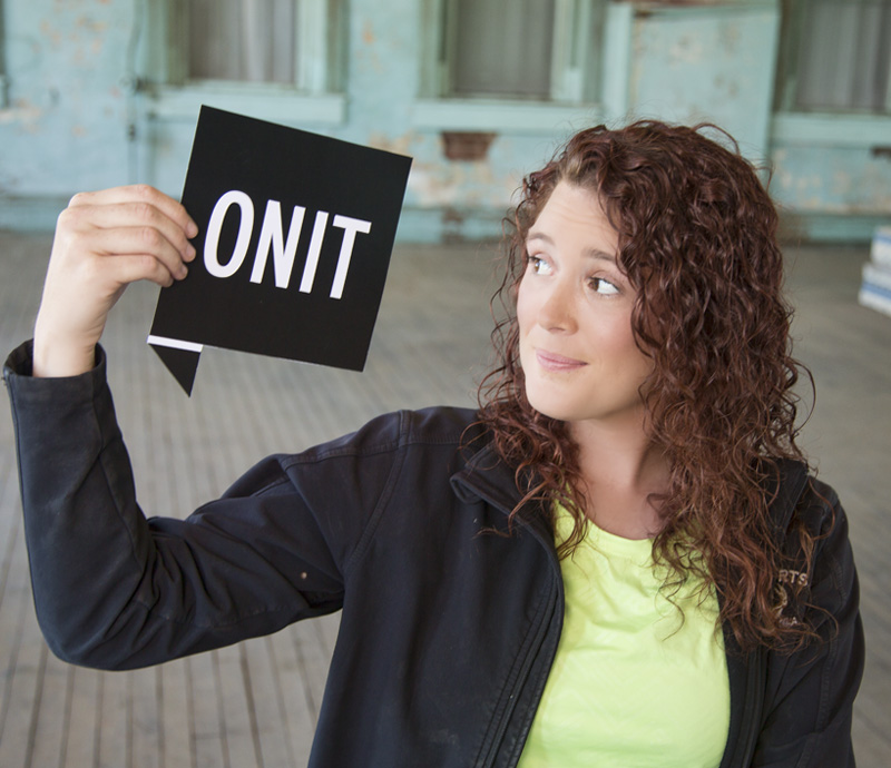 "Female youth hold a black sign that has ""ONIT"" on it"
