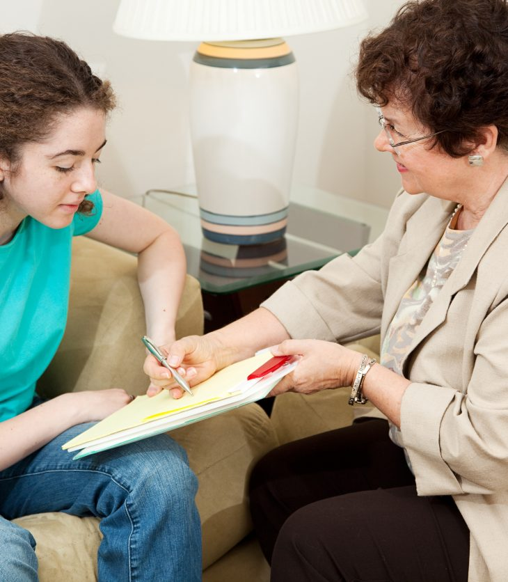 Psychologist giving a teen girl an agreement to sign before starting therapy.