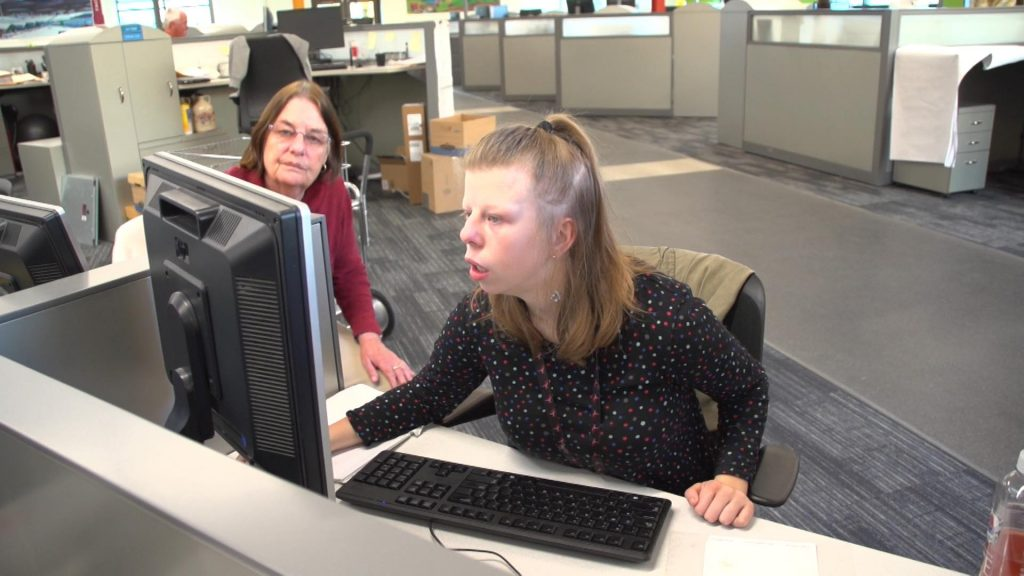Female youth working on a computer with the assistance of a female adult