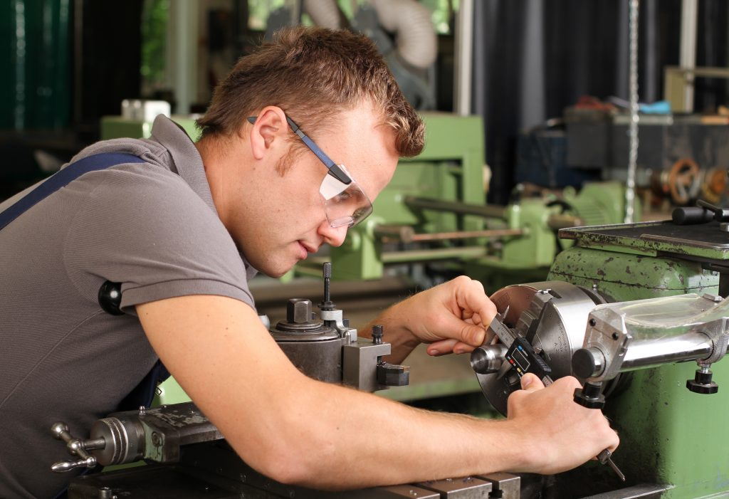 Young man working at a mechanic workshop class