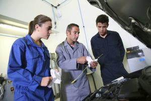 Instructor with students in repair shop changing motor oil